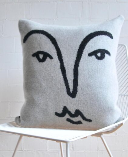 Merino wool cushion with face outlined in black